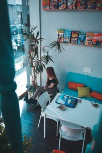 woman sitting near table under shelves with boxes